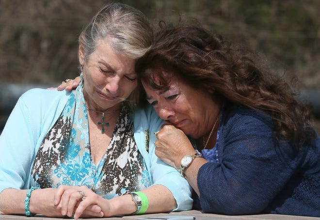 Kim Shama-Hanna is comforted by her sister, Cindi Shama, Tuesday in Akron. State COVID-19 protocols have kept all but one family member from visiting their 96-year-old mom in the hospital.