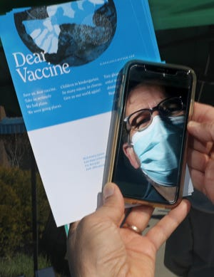 "David Hassler, director of Kent State University's Wick Poetry Center, is reflected in a cellphone as he talks about ""Dear Vaccine"" outside the Kent State Field House mass vaccination site Tuesday."