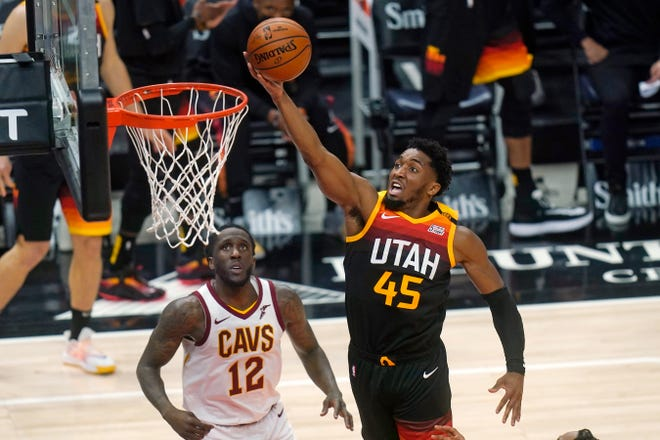 Utah Jazz guard Donovan Mitchell (45) goes to the basket as Cleveland Cavaliers forward Taurean Prince (12) looks on in the first half during an NBA basketball game Monday, March 29, 2021, in Salt Lake City. [Rick Bowmer/Associated Press]