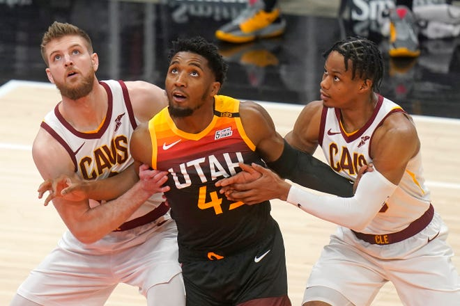 Cleveland Cavaliers' Dean Wade, left, and Isaac Okoro, right, battle under the boards with Utah Jazz guard Donovan Mitchell, center, in the first half during an NBA basketball game Monday, March 29, 2021, in Salt Lake City. (AP Photo/Rick Bowmer)