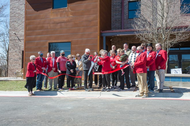 The ribbon is cut outside the Ronald McDonald House for its grand reopening, attended by staff and Amarillo Chamber of Commerce members on Tuesday.