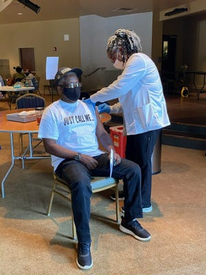 Roderick Whitlock, 66, receives his first COVID-19 vaccine shot from nurse manager Danette Thomas in March at a University Hospital event.
