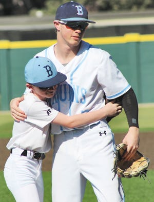 """Bartlesville High junior Bradee Rigdon, right, and his younger brother Cy embrace following the ceremonial pitch Monday at Bill Doenges Memorial Stadium. A few minutes earlier, the diamond had been officially named """"Rigdon Field"""" in honor of their father Spence Rigdon the former Bartlesville High head baseball coach who passed away in 2019."""