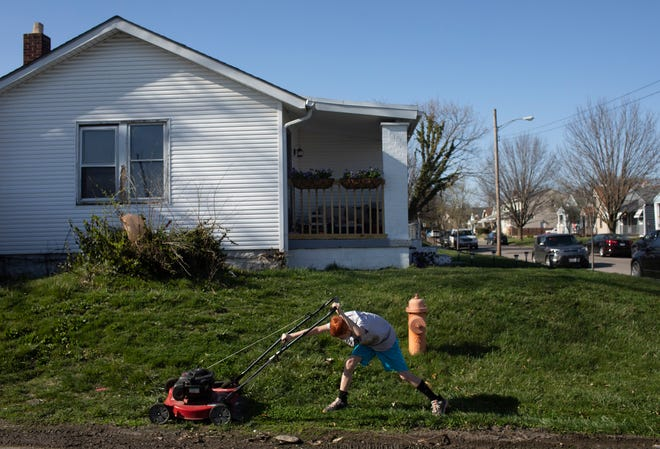 Preston Long, 11, shoves the lawnmower with his foot to keep it going in the front yard of Michael Bayer and Heather Stockton's home in the Hilltop neighborhood of Columbus, Ohio on March 27. Long has been spending weekends helping Bayer clean up his backyard in return for payment, which he is hoping to use for his Aunt to afford a new apartment.