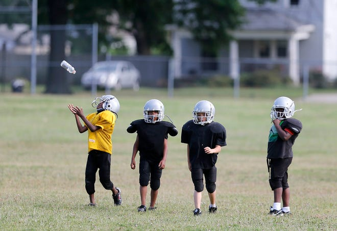 In this 2016 photo, 7- and 8-year-old boys who play for the LGY Rockets take a break from football practice at Linden Recreation Center. A major study of Columbus youth sports released Tuesday finds that most kids play sports to be with their friends.