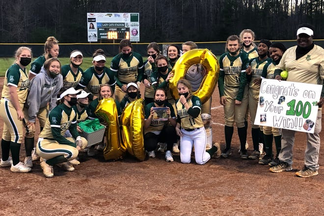 Eastern Randolph's softball team celebrates coach LaVette Graham's 100th career victory following the Wildcats' 10-0 win over Jordan-Matthews on Monday. [Cecil Mock for The Courier-Tribune]