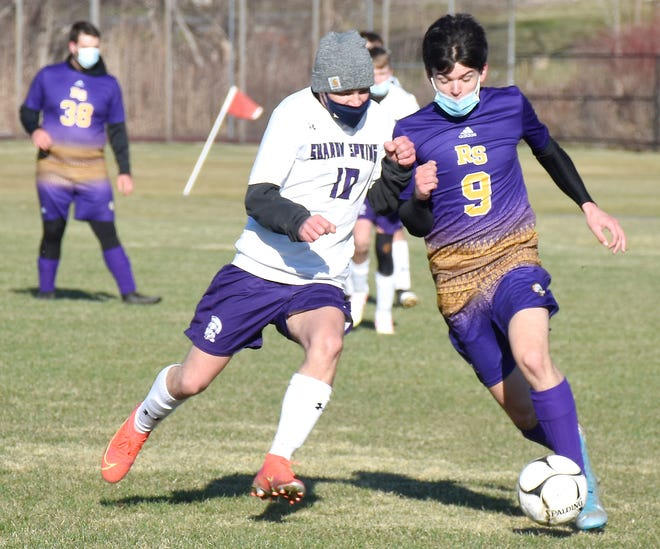 Richfield Springs Indian Connor Scheffler (9) holds off a Sharon Springs defender while making a run at the goal during the first half of Monday's match.