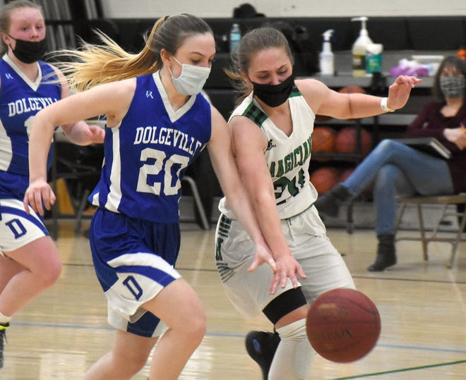 Dolgeville's Phoenix Longway (20) and Herkimer's Taylor Smith pursue a loose ball during the second half of Monday's game.