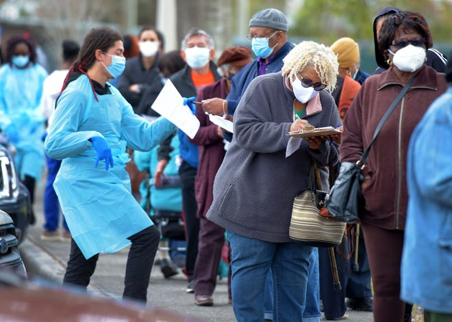 Health care workers help those in line fill out their paperwork as they wait to get their COVID-19 vaccination on Feb. 5 outside the Clanzel T. Brown Senior Center on Moncrief Road in Jacksonville.