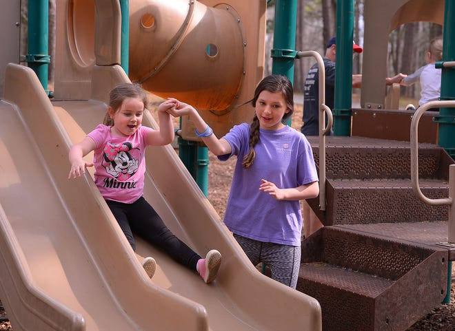 Visitors enjoy a spring weekend at Croft State Park in Croft, Saturday, March 27, 2021. McKennon Dill, 11, helps her sister Isabelle, 4, as they enjoy the playground area at the park.