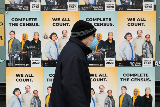 In this April 1, 2020 photo, a man wearing a mask walks past posters encouraging participation in the 2020 Census in Seattle's Capitol Hill neighborhood. A delay in census data is scrambling plans in some states to redraw districts for the U.S. House and state legislatures. The Census Bureau has said redistricting data that was supposed to be provided to states by the end of March won't be ready until August or September. (AP Photo/Ted S. Warren, File)