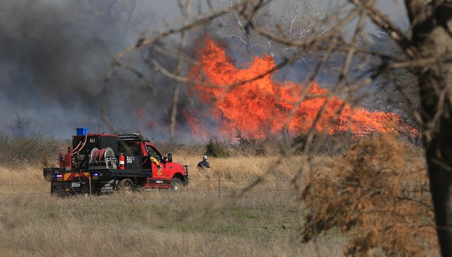 Brush truck 61 drives toward a brush fire south of 30th Avenue Monday afternoon. More than 600 acres were burned Monday between 4th and 30th Avenues and north of 95th and Plum.