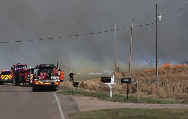 Firefighters spray water on a grass fire in the 7500 block of East 30th Ave. Monday afternoon. The fire started on 4th Ave. and burned about three miles north.
