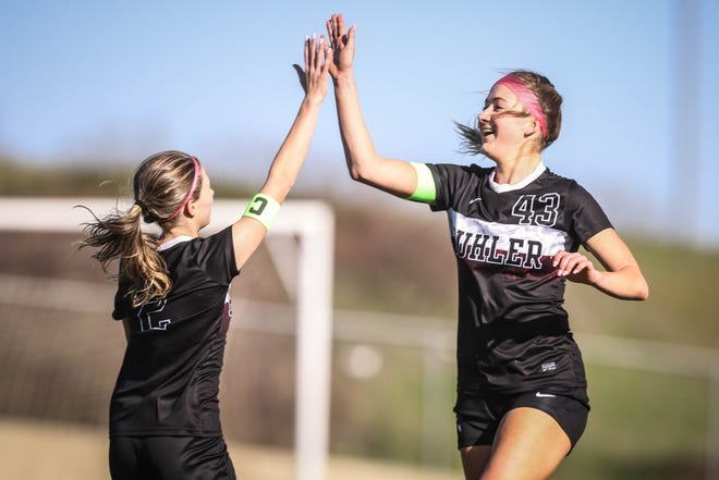 Buhler's Alexis Hutton high-fives Amaleigh Mattison after scoring a goal against Arkansas City in the Goddard tournament.