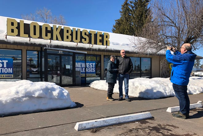 FILE - In this March 11, 2019, file photo Debby Saltzman, of Bend, Ore., poses for a photo, in front of the last Blockbuster store with her twin brother, Michael, visiting from Melbourne, Australia, in Bend, Ore. Taking the photo is Saltzman's husband, Jeremy Saltzman. The new Netflix movie called The Last Blockbuster that began airing March 15, 2021 is generating interest in the store, which became the last Blockbuster location on Earth when a location in Perth, Australia shut its doors in 2019. (AP Photo/Gillian Flaccus)