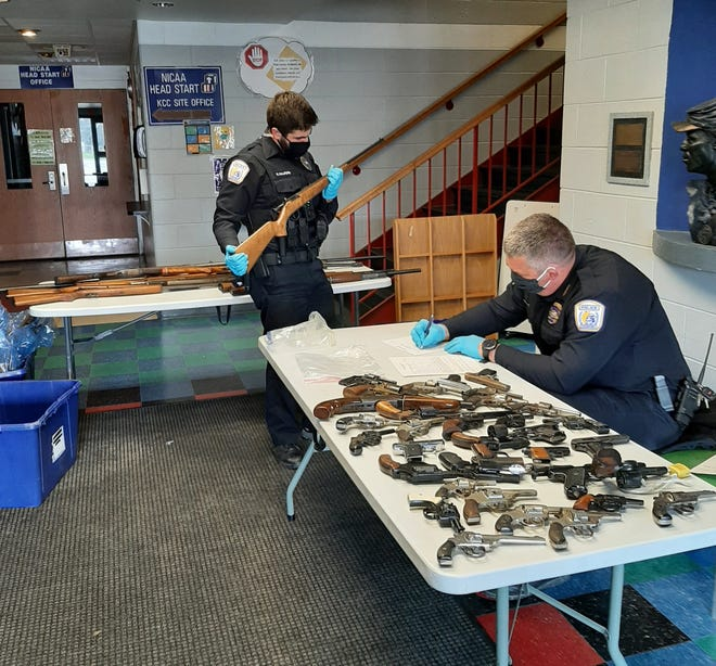 Freeport Police Chief Matt Summers, right, and Officer Rob Halford inventory guns that were collected in a gun buyback event Saturday, March 27, 2021, where 48 guns were turned in for cash.
