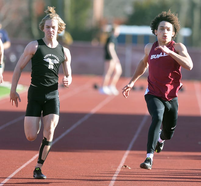 Newton sprinter Curt Claussen, left, challenges Buhler's Diante Campbell in the 100-meter dash during the Newton Invitational. Campbell won both the 100- and 200-meter dash in the meet. Claussen finished third in both events.