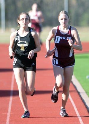 Newton junior Oliva Adams, left, duels Buhler senior Allison Willm in the anchor leg of the 4x800-meter relay at the Newton Invitational. Adams pulled away on the final lap for the win.