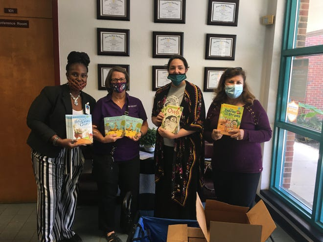 Blake Academy Principal Myra Richardson, Sheri Geiger of USBorne Books, Blake Academy academic interventionist Tasha Look, and Paula Dockery with Lakeland Kiwanis Club hold up donated books in the school's office.