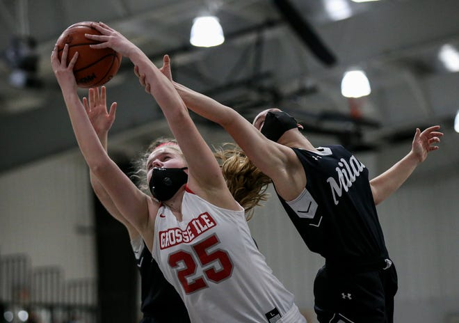Milan's Lauryn Obey (right) reaches back to try and stop Grosse Ile's Ashlyn Weatherly during the third quarter Monday, March 29, 2021 in the Division 2 Regional semifinals.
