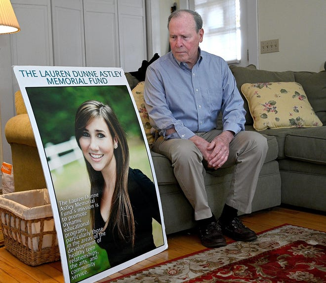 Malcolm Astley poses with a photograph of his daughter, Lauren Dunne Astley, in 2019.