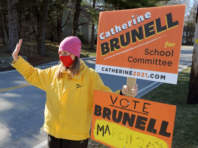 Catherine Brunell, a candidate for School Committee, waves to passing voters while outside Natick High School on Election Day on Tuesday. Brunell won one of two available seats on the board.