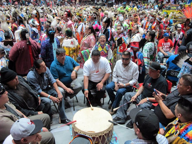 In this 2013 file photo, a steady stream of Native American and Indigenous dancers file past a drumming group at the 30th annual Gathering of Nations in Albuquerque, N.M. The drum is at the heart of Native American communities, and just like the drum, Native women radiate at the heart of their families and communities.