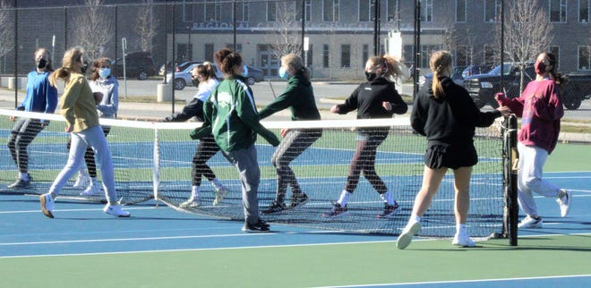 Members of the Dover High School girls tennis team get in some running at Monday's first day of practice.