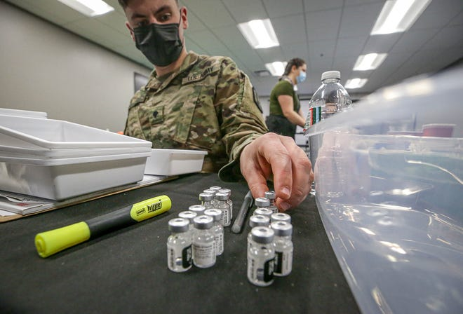 National Guard troops prepare vaccination kits in a back room at The Dunk.