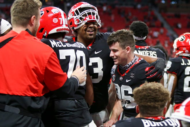 Jan 1, 2021; Atlanta, GA, USA; Georgia Bulldogs place kicker Jack Podlesny (96) is congratulated by offensive lineman Xavier Truss (73) after a game winning field goal against the Cincinnati Bearcats in the second half of the Chick-fil-A Peach Bowl at Mercedes-Benz Stadium. Mandatory Credit: Brett Davis-USA TODAY Sports