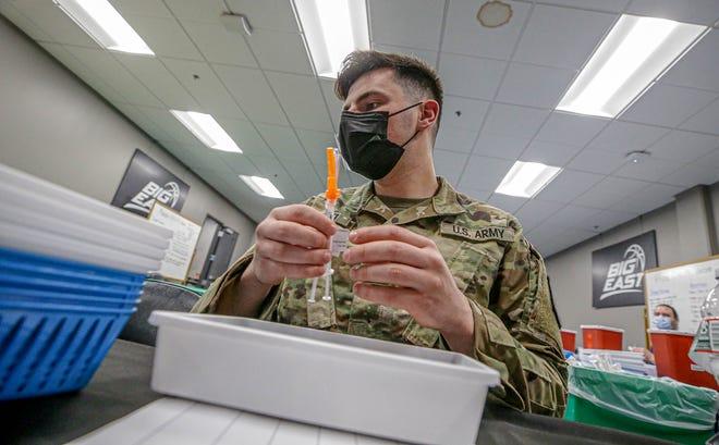 National guardsman prepare vaccination kits.