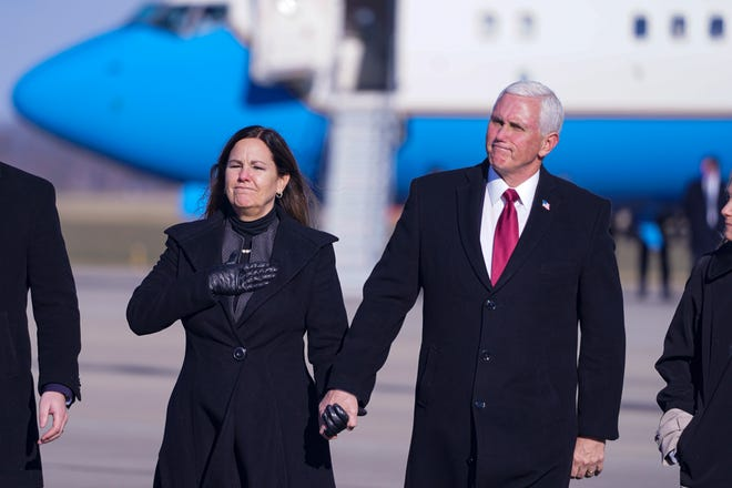 FILE - In this Jan. 20, 2021, file photo, former Vice President Mike Pence and his wife Karen walk from the plane to greet supporters after arriving back in his hometown of Columbus, Ind. Pence is steadily re-entering public life as he eyes a potential run for the White House in 2024. He's writing op-eds, delivering speeches, preparing trips to early voting states and launching an advocacy group likely to focus on promoting the accomplishments of the Trump administration. (AP Photo/Michael Conroy, File)