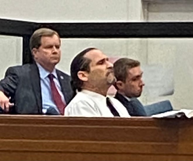 Defendant Jeffrey Acker looks toward the ceiling as he hears his guilty verdict. District Attorneys Scott Thomas is seen sitting behind him.