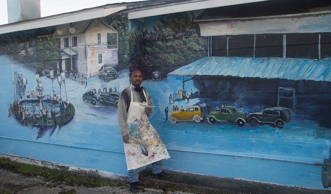 New Bern artist Lee Hood with his mural of 1930s Queen and Pollock streets.
