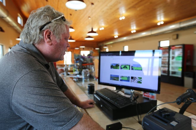 Rick Farrant scrolls through a list of simulated games guests will soon be able to play at GreatLIFE North's Toptracer Range. Farrant and his wife, Linda, are hoping to stand up Toptracer, a division of Topgolf, at the North Topeka GreatLIFE by the end of May.