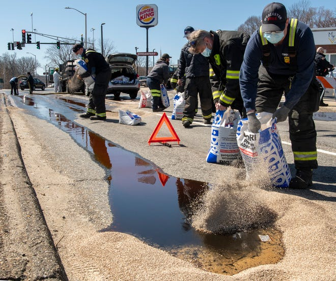Worcester firefighters spread absorbent material into a spill of used cooking oil on Park Avenue at Webster Square Tuesday. An estimated 50-100 gallons of oil spilled from a tank on a truck.