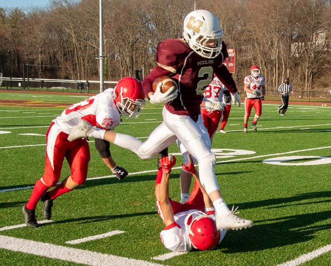 Millbury's Lucas Friedman runs through two Southbridge would-be tacklers during the season opener.