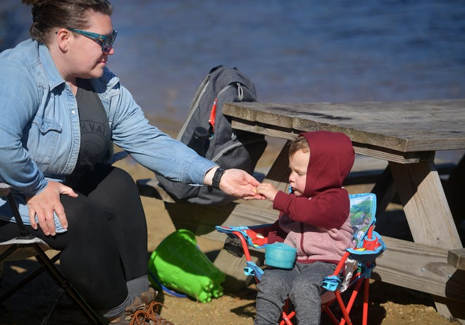 Leigh Soucy of Worcester accepts a yogurt covered raisin from her son Felix Kobialka, 3, Tuesday at the beach at Rutland State Park.