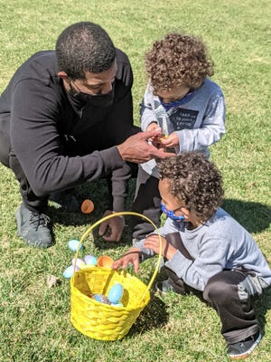 Walter Correia, of Clinton, helps his son, Maxwell, 2, open an Easter egg while his wother son, Michael, 4, plays with the rest of the eggs. The family took part in the Clinton Parks and Recreation Easter Egg hunt Saturday, March 27.
