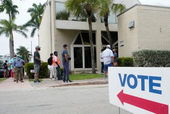 People wait in line to vote outside of an early voting site in Miami Beach on Oct. 20.