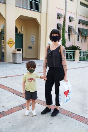 This photo of a woman with child was taken outside of the Headquarters Library in downtown Gainesville when they were there to pick-up material through outside services. The woman alone is working on a virtual program,.