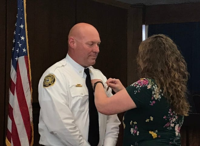 Gadsden's new fire chief Wil Reed gets his new badge, pinned on by his wife Kristie Reed.