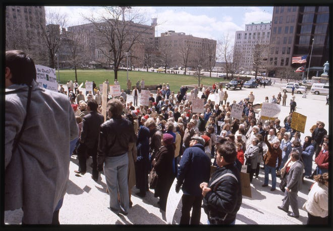 On March 20, 1985, protestors gathered outside the Ohio Statehouse to protest the closing of Home State Savings Bank. The bank, headquartered in Cincinnati, had 10 Columbus branches. The bank, which was insured by the Ohio Deposit Guarantee Fund, closed March 9 after ESM Government Securities Inc. of Fort Lauderdale, Florida, its securities brokerage firm, was closed by the Securities and Exchange Commission. On March 15, Gov. Dick Celeste declared a three-day banking holiday for other state-insured savings institutions until they could be insured by the federal government. Ohio eventually reimbursed all Home State Savings Bank depositors for a total of $12 million.
