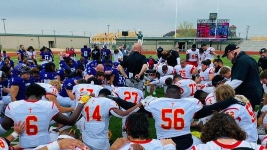 Football players from Southwestern Assemblies of God University and Arizona Christian University gather on the field for a prayer after Saturday's game. ACU edged the Lions, 23-20.