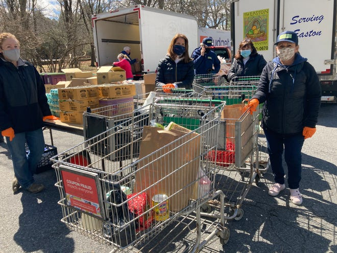 Easton Food Pantry volunteers, from left, Regis Tagliamont, Tricia Connolly and Helen Tobey help distributed Easter meals Monday, March 29 at the Easton Food Pantry at Town Hall.