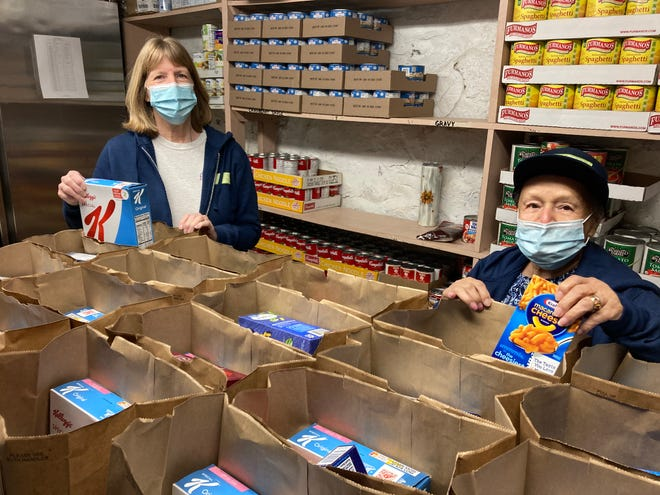 Easton Food Pantry volunteers Diane Kent, left, and Gigi Rivera, fill bags of food to distribute March 26.