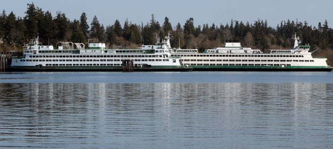 The Washington State Ferry Elwha sits docked in the foreground as the Puyallup pulls away from the Bainbridge Island Ferry Terminal on March 30.