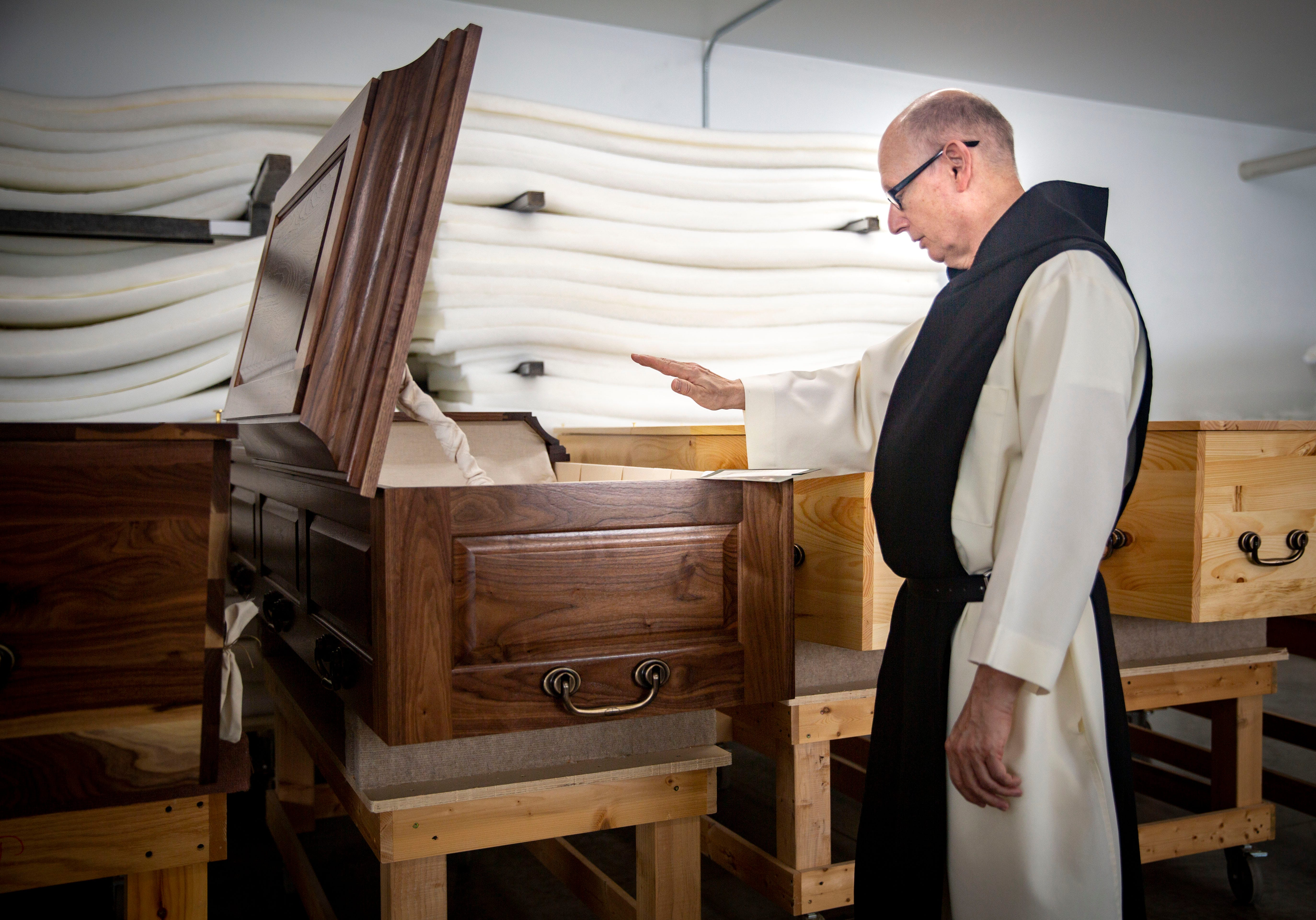 Trappist monk Brother Paul-Andrew Tanner blesses a casket in the Trappist Caskets workshop near the New Melleray Abbey southwest of Dubuque on March 16, 2021.