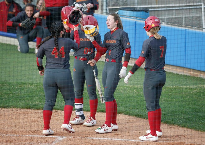 Members of the Iowa State softball team celebrate at home plate after junior Mikayla Ramos hit a home run against Drake at Drake University in Des Moines on Tuesday, March 30, 2021.