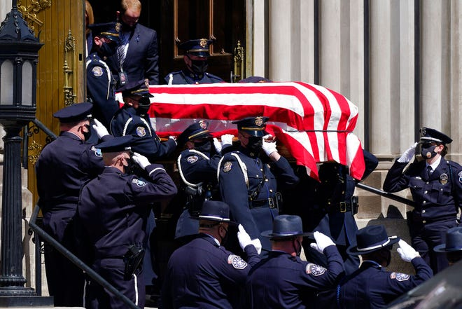 Peti mati yang membawa mayat Boulder yang jatuh, Colorado, petugas Departemen Kepolisian Eric Talley dibawa oleh penjaga kehormatan Polisi Denver ke mobil jenazah yang menunggu setelah kebaktian.